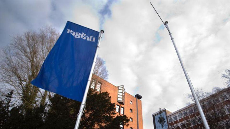 Eine Firmenflagge weht vor dem Hauptsitz des Unternehmens Drägerwerk. Foto: picture alliance / dpa/Archivbild