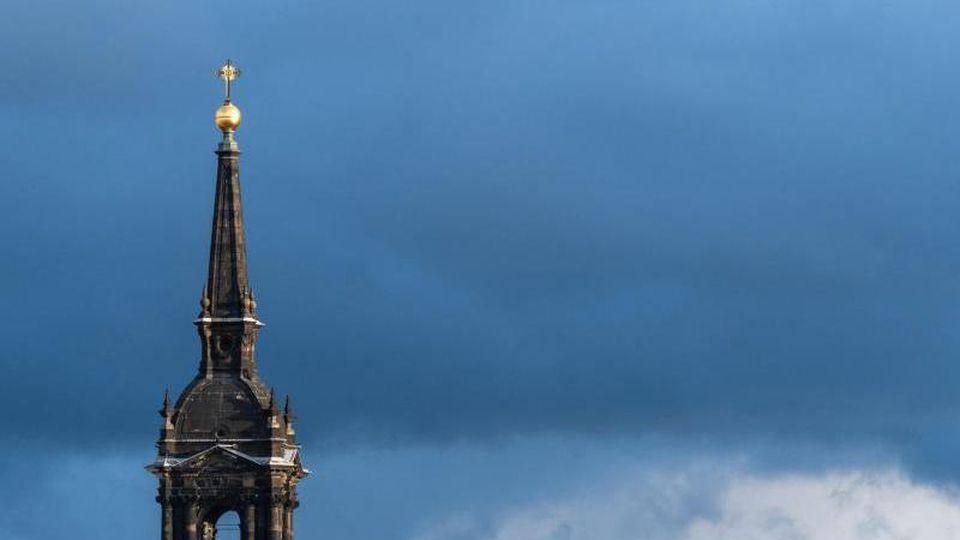 Die Spitze der Dreikönigskirche in Dresden vor Wolkenhimmel. Foto: Robert Michael/dpa-Zentralbild/ZB/Archiv