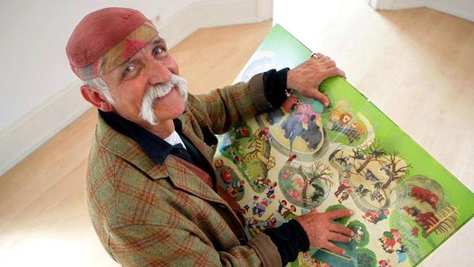 Ali Mitgutsch hält im Bilderbuchmuseum eines seiner Kinderbücher in den Händen. Foto: Rolf Vennenbernd/dpa/Archivbild
