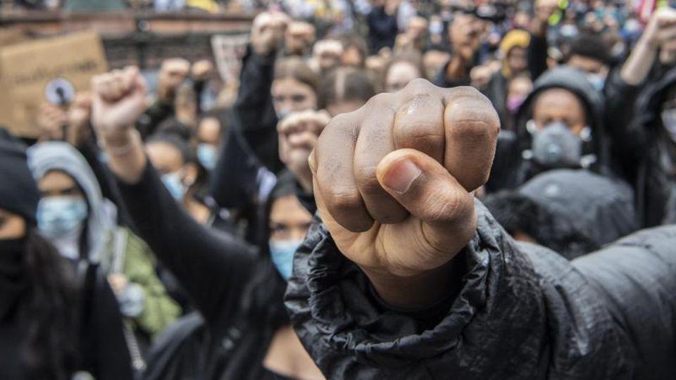 Auf Knien und mit in die Höhe gestreckter Faust bekunden Demonstranten auf dem Römerberg in Frankfurt ihre Solidarität mit den Anti-Rassismus-Protesten in den USA. Foto: Boris Roessler/dpa