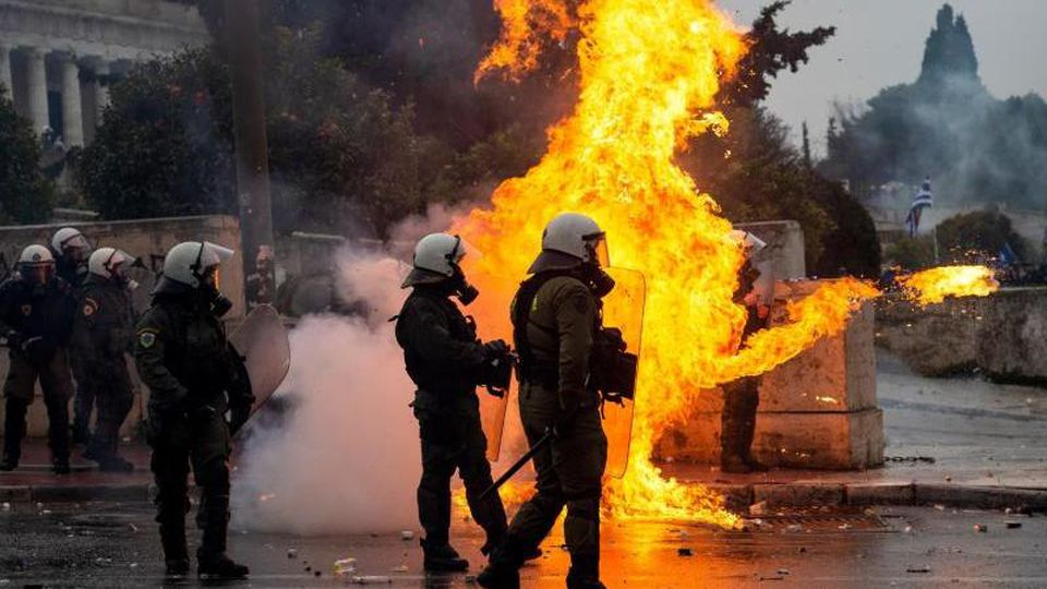 Griechische Bereitschaftspolizisten stehen vor einer Feuerwand, verursacht durch einen Molotow-Cocktail. Foto: Angelos Tzortzinis