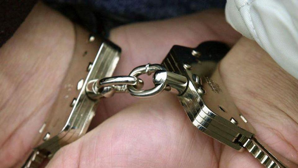 Ein mann wird in Handschellen abgeführt. Foto: Boris Roessler/dpa/Symbolbild