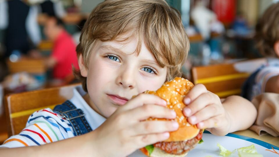 Junge isst Burger.