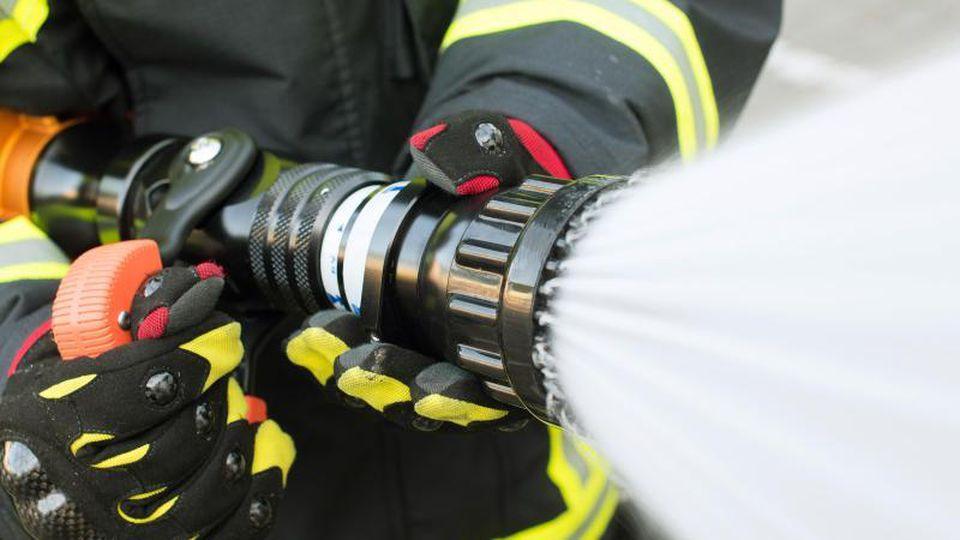 Ein Feuerwehrmann hält einen Löschschlauch in der Hand. Foto: Daniel Bockwoldt/Archivbild