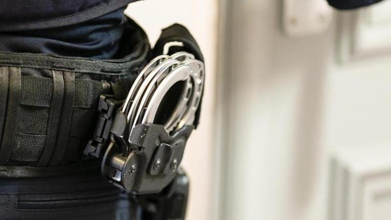 Handschellen sind an einem Gürtel befestigt. Foto: Frank Molter/dpa/Symbolbild