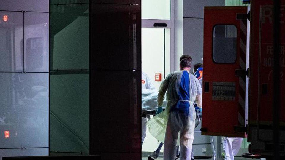 Mitarbeiter aus dem Leber- und Infektionszentrum des Universitätsklinikums in Düsseldorf nehmen den ersten mit dem Coronavirus Infizierten in NRW in Empfang. Foto: Guido Kirchner/dpa
