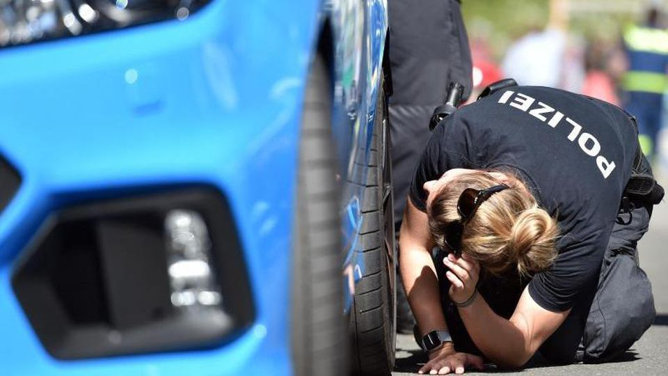 """Eine Polizistin kontrolliert am """"Car-Freitag"""" im April 2019 die Reifen eines getunten Autos. Foto: Caroline Seidel/dpa/Archivbild"""