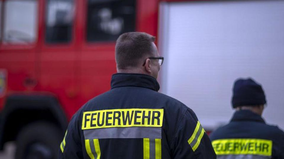 Feuerwehrmänner stehen vor einem Feuerwehrauto. Foto: Jens Büttner/zb/dpa/archivbild