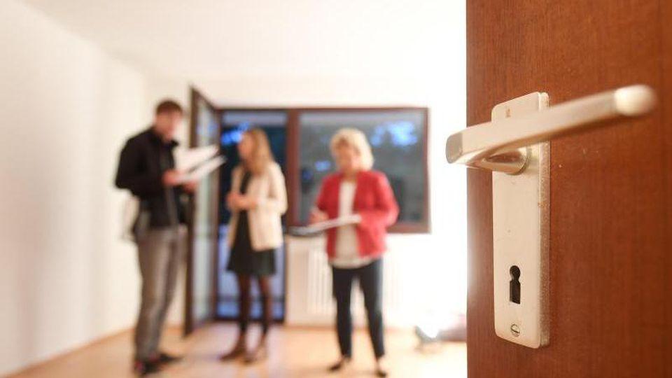 Eine Maklerin spricht mit Interessenten bei einer Wohnungsbesichtigung. Foto: Tobias Hase/dpa