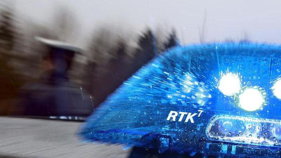 Ein Polizist steht neben einem Streifenwagen. Foto: Karl-Josef Hildenbrand/dpa/Archivbild