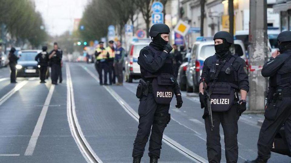 Polizisten stehen mit Maschinenpistolen auf der Eisenbahnstraße in Leipzig. Foto: Peter Endig/dpa-Zentralbild/dpa