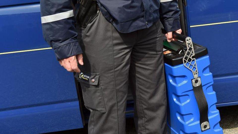 Ein Mitarbeiter der Sicherheitsfirma Kötter hält eine Geldkassette. Foto:Caroline Seidel/Archivbild