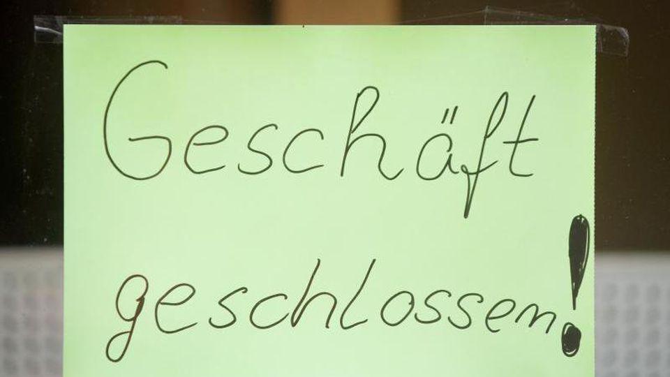 """""""Geschäft geschlossen"""" steht an einem leer stehenden Ladengeschäft. Foto: Swen Pförtner/dpa/Archivbild"""