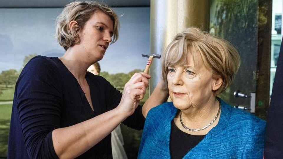 Maskenbildnerin Henriette Masmeier nagelt der Puppe der Bundeskanzlerin Angela Merkel die Perücke auf den Wachskopf. Foto: Markus Scholz/dpa