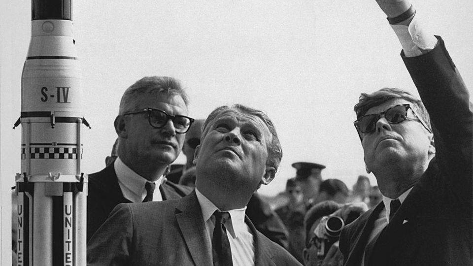 ARCHIV - 15.11.1963, USA, Cape Canaveral: Wernher von Braun (M), Raketenkonstrukteur aus Deutschland steht neben dem damaligen US-Präsidenten John F. Kennedy und erklärt ihm das Saturn-Startsystem. Foto: -/Nasa Headquarters HO/dpa - ACHTUNG: Nur zur