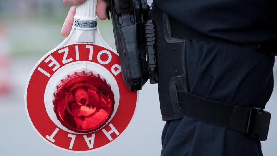 """Ein Polizist hält eine Kelle mit der Aufschrift """"Halt. Polizei"""" in der Hand. Foto: Sven Hoppe/dpa/Symbolbild"""