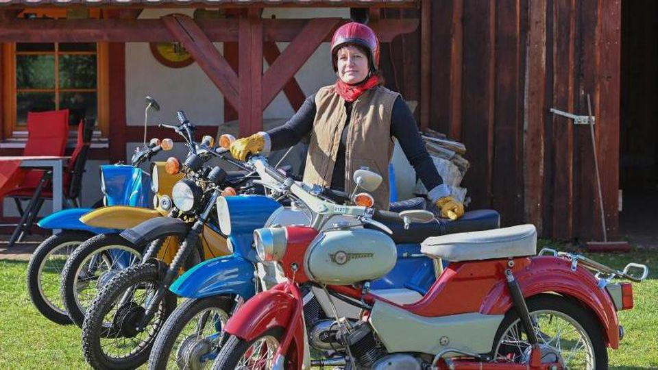 Silke Gute steht zwischen verschieden Mopeds aus DDR-Zeiten. Foto: Patrick Pleul/dpa-Zentralbild/dpa