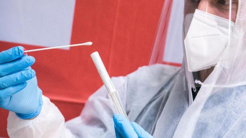 Ein Mitarbeiter des Deutschen Roten Kreuzes (DRK) steht in einem Corona-Testzentrum und hält einen Test. Foto: Daniel Bockwoldt/dpa/Archiv