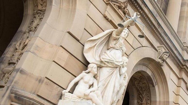 Eine Statue der Justitia hält eine Waagschale. Foto: Stefan Puchner/dpa/Symbolbild