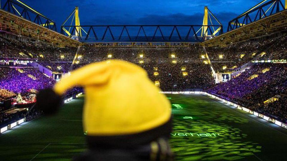 BVB-Fans singen gemeinsam im Signal Iduna Park Weihnachtslieder. Foto: Bernd Thissen/dpa