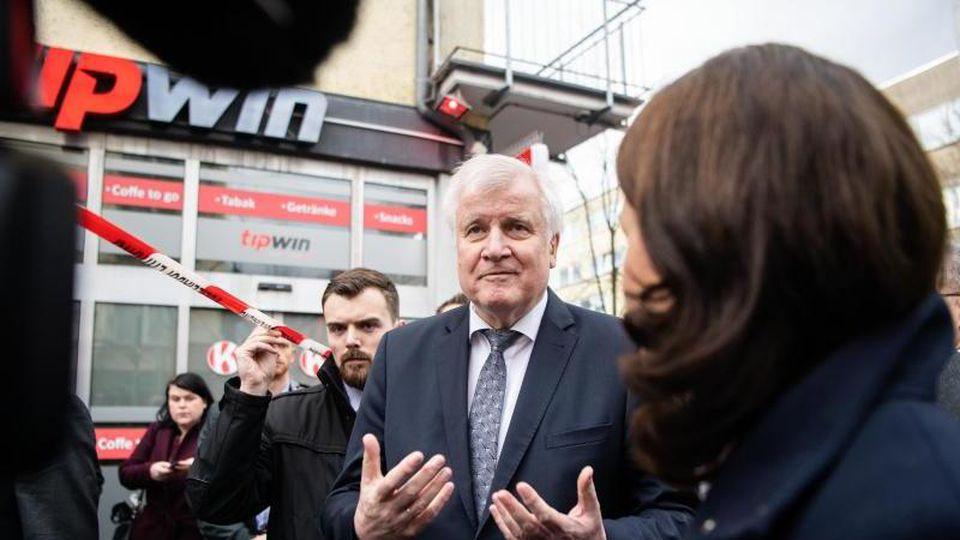 Horst Seehofer (CSU, r), Bundesinnenminister, steht am Heumarkt in unmittelbarer Nähe eines Tatorts vor den Journalisten. Foto: Andreas Arnold/dpa/Archivbild