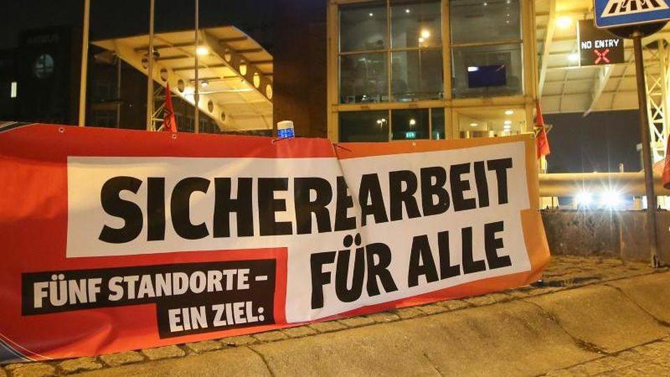 """Ein Transparent mit der Aufschrift """"Sichere Arbeit für Alle"""" hängt vor den Werkstoren des Flugzeugherstellers Airbus in Hamburg-Finkenwerder. Foto: Bodo Marks/dpa"""