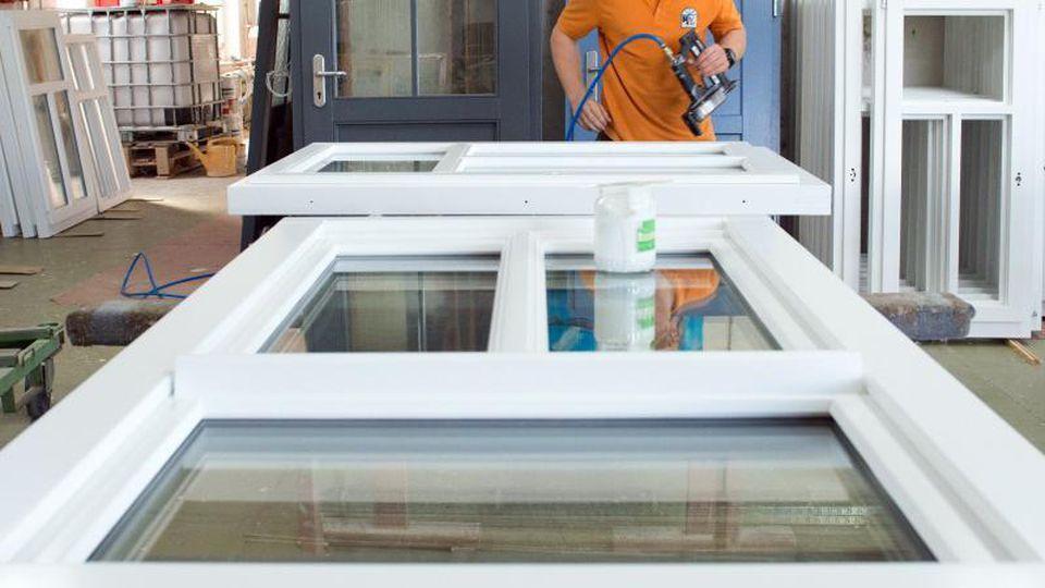 Ein Auszubildender befestigt Glasleisten an einem Fensterrahmen. Foto: Sebastian Kahnert/zb/dpa/Archivbild