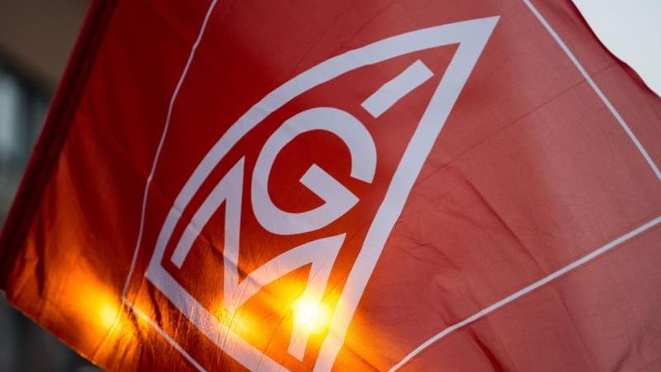 Eine Fahne mit dem Logo der IG-Metall wird geschwenkt. Foto: Lino Mirgeler/Archivbild