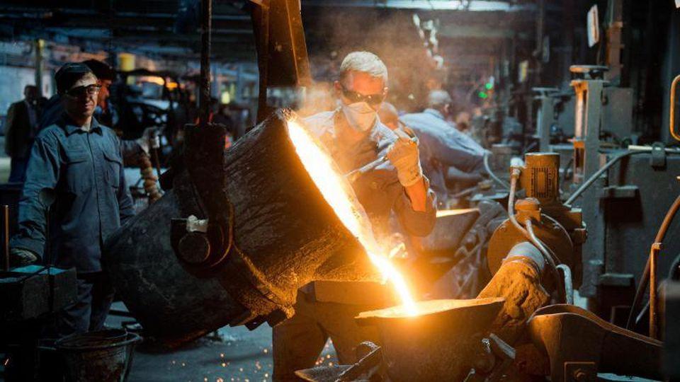 Ein Mitarbeiter gießt flüssiges Gusseisen im Werk eines Autozulieferers. Foto:Julian Stratenschulte/Archiv