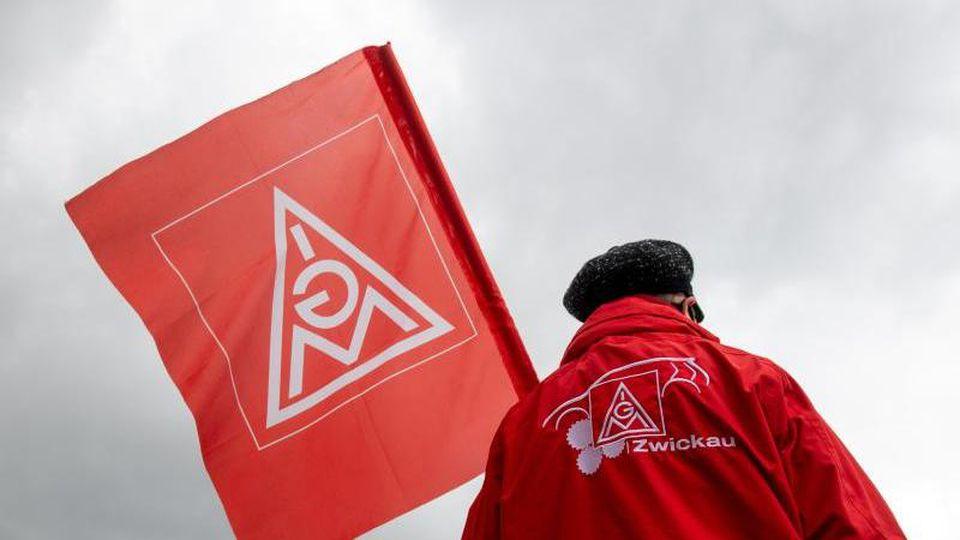 Mit einer Fahne der IG Metall beteiligt sich eine Frau am Warnstreik. Foto: Hendrik Schmidt/dpa-Zentralbild/dpa/Archivbild