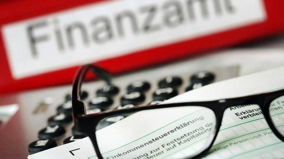 Auf einem Vordruck für die Steuererklärung liegen ein Stift und eine Brille. Foto: Oliver Berg/Archiv