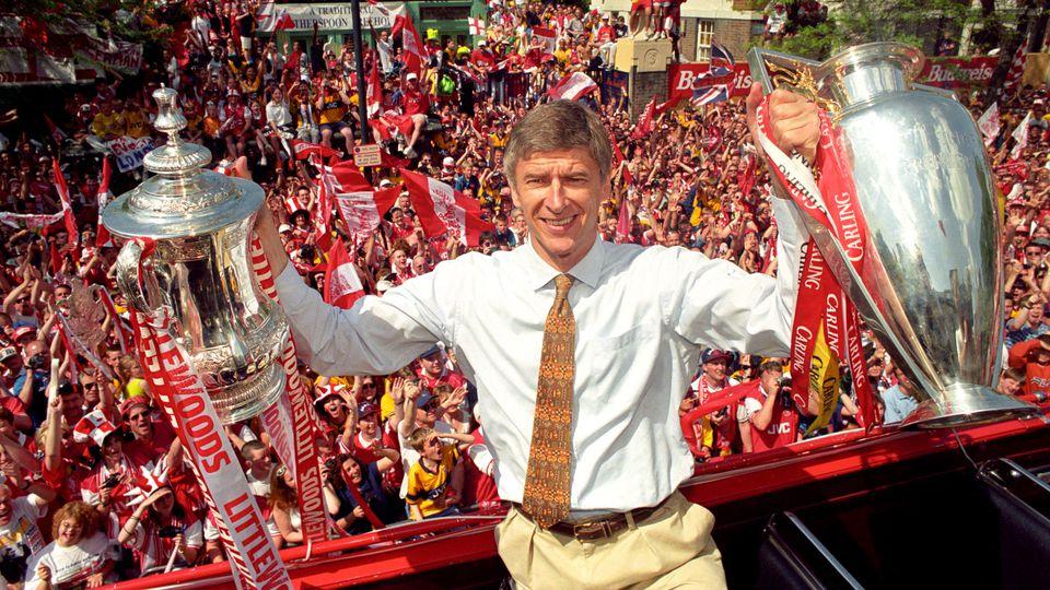 ARCHIV - 17.05.1998, Großbritannien, London: Arsène Wenger, Trainer des FC Arsenal, hält die Pokale vom FA Cup und vom League Cup, während im Hintergrund die Fans jubeln. Arsène Wenger hört nach fast 22 Jahren als Trainer des FC Arsenal am Ende diese