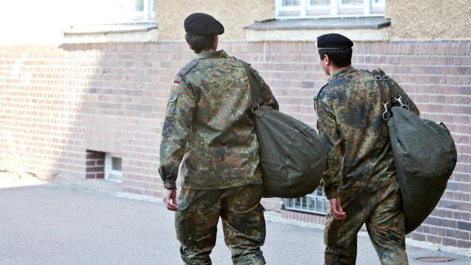 Zwei ausscheidende Wehrdienstleistende verlassen nach ihrer offiziellen Verabschiedung die Kaserne. Foto: Daniel Karmann/dpa/Archivbild