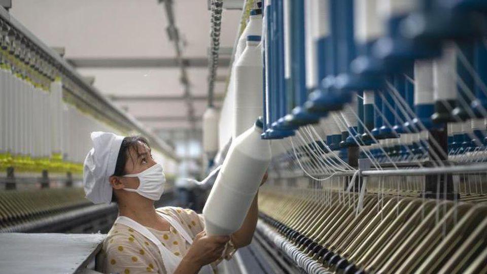 Eine Frau arbeitet in einer Textilfabrik in der ostchinesischen Provinz Jiangsu. Foto: CHINATOPIX/AP/dpa