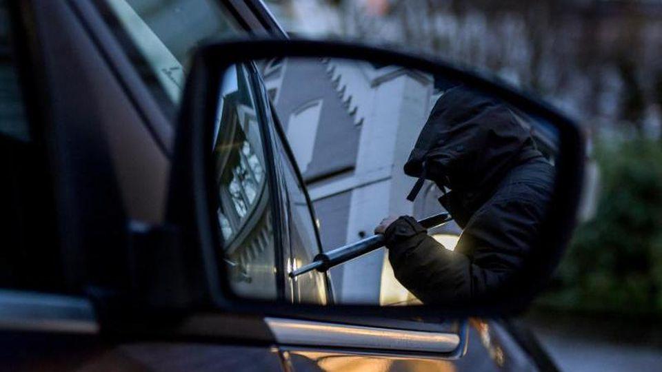 Ein Mann versucht eine Autotür mit einer Metallstange aufzubrechen (gestellte Szene). Foto: Axel Heimken/dpa/Symbolbild