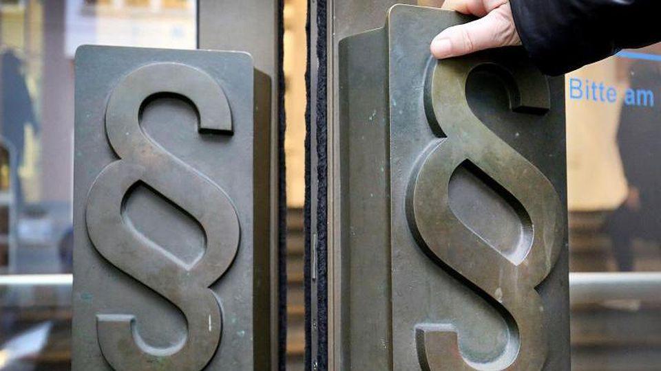 Paragrafen-Symbole sind an Türgriffen am Eingang zum Landgericht angebracht. Foto: Oliver Berg/dpa/Symbolbild