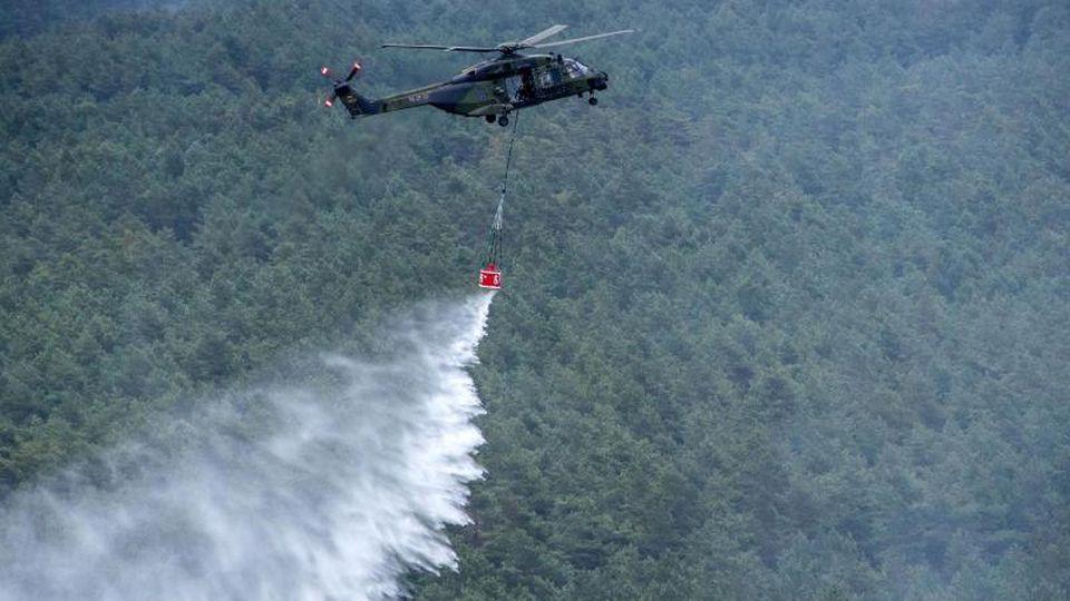 Ein Hubschrauber mit einem Löschwasser-Behälter wirft über einer Brandstelle das Löschwasser ab (Luftaufnahme aus einem Hubschrauber). Foto: Jens Büttner/Archivbild