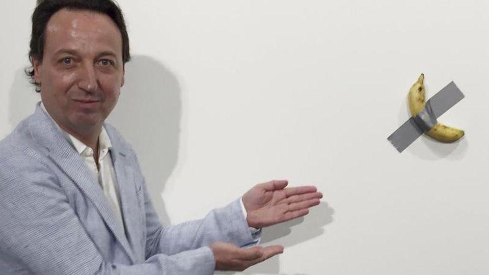 """Galerist Emmanuel Perrotin zeigt auf das Kunstwerk """"Comedian"""" von Maurizio Cattelan auf der Art Basel in Miami. Foto: Siobhan Morrissey/AP/dpa"""