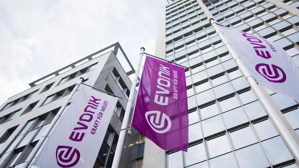 Flaggen wehen vor der Zentrale des Spezialchemiekonzerns Evonik. Foto: Rolf Vennenbernd/dpa/Archivbild