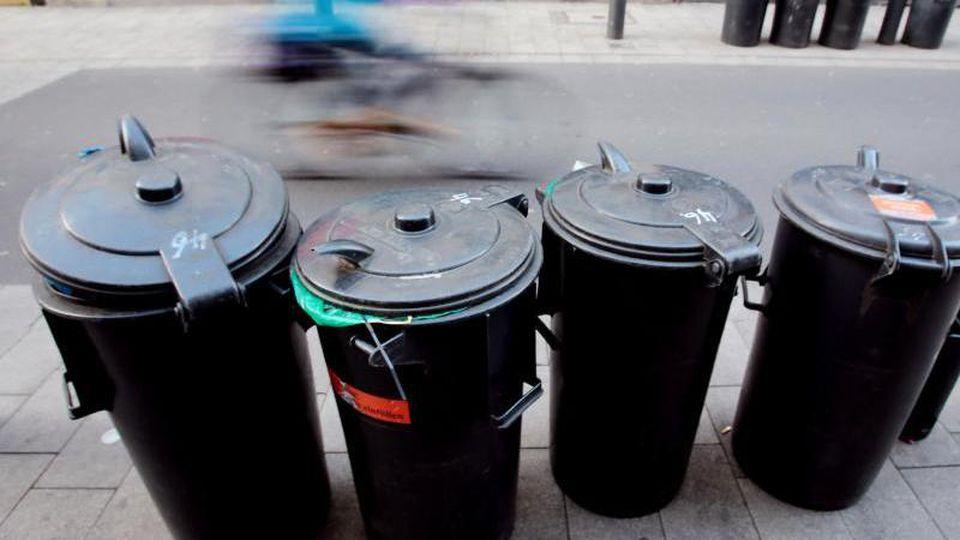 Mülltonnen stehen am Straßenrand. Foto: Oliver Berg/Archivbild