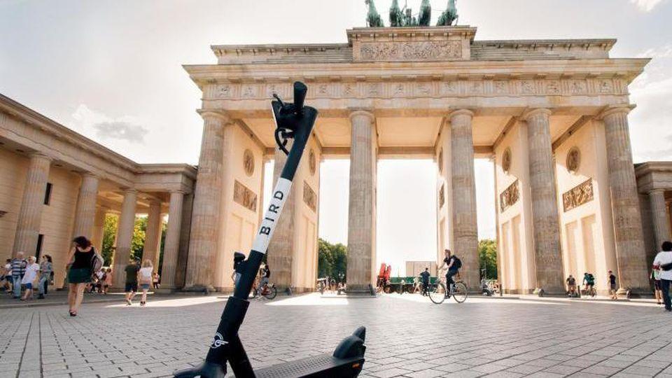 Ein E-Tretroller des Anbieters Bird steht vor dem Brandenburger Tor. Die US-Firma, die bereits in 140 Städten weltweit aktiv ist, startet an diesem Montag in Berlin, Hamburg, Köln, Frankfurt und München mit zunächst jeweils 100 Scootern. Foto: Bird/Hand