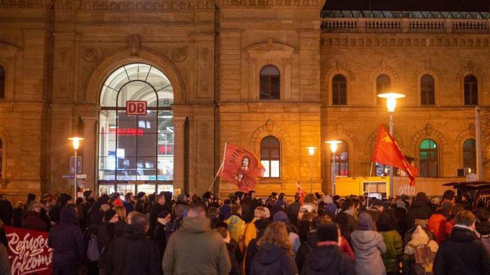 Demonstranten stehen mit roten Fahnen vor dem Hauptbahnhof. Foto: Klaus-Dietmar Gabbert/dpa-Zentralbild/dpa