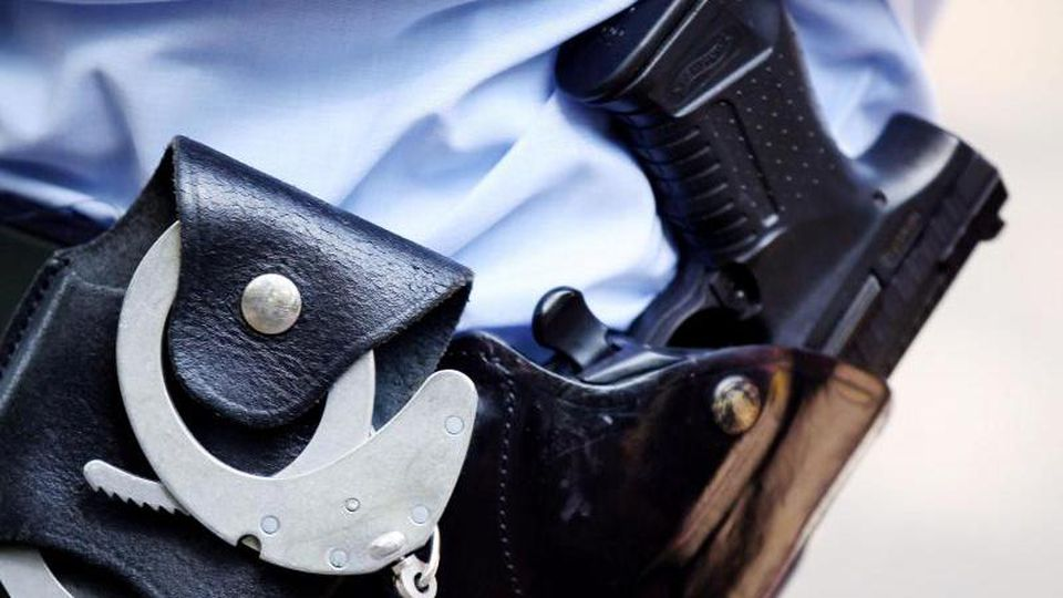 Handschellen und Pistole am Gürtel eines Polizisten. Foto: Oliver Berg/dpa/Archivbild