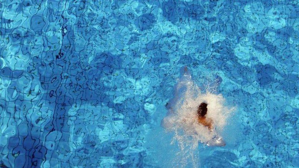 Ein Junge springt im Sommerbad Neukölln vom Sprungturm ins Wasser. Foto: Johannes Eisele/dpa-Zentralbild/dpa