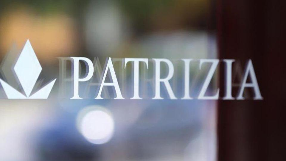 Logo und Schriftzug des Immobilienkonzerns Patrizia an der Eingangstür der Hauptverwaltung. Foto: Karl-Josef Hildenbrand/dpa/Archivbild