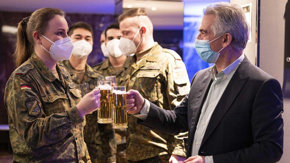 Oberbügermeister Peter Feldmann übergibt den Bundeswehrsoldaten einen Kasten Bier, aufgenommen am Sonntag (28.02.2021) in Frankfurt am Main. Foto: Salome Roessler / lensandlight