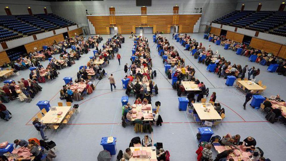 Freiwillige sortieren Stimmzettel in der Alsterdorfer Sporthalle. Foto: Georg Wendt/dpa