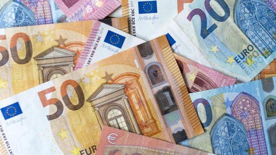 Zahlreiche Banknoten zu 10, 20 und 50 Euro liegen auf einem Tisch. Foto: Monika Skolimowska/dpa-Zentralbild/dpa/Illustration