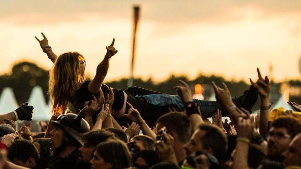 Während eines Konzerts wird auf dem Festivalgelände des Wacken Open Air ein Fan beim Crowd-Surfing auf Händen getragen. Foto: Christophe Gateau/dpa/Archivbild