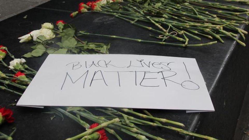 """Blumen und ein Schild mit der Aufschrift """"Black Lives Matter!"""". Foto: Christina Horsten/dpa/Archivbild"""